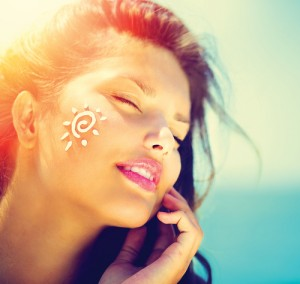 Beautiful happy cute Girl applying Sun Tan Cream on her Face over ocean background