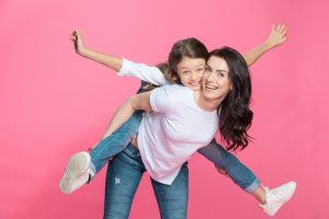 Happy mother piggybacking adorable little daughter smiling at camera-img-blog