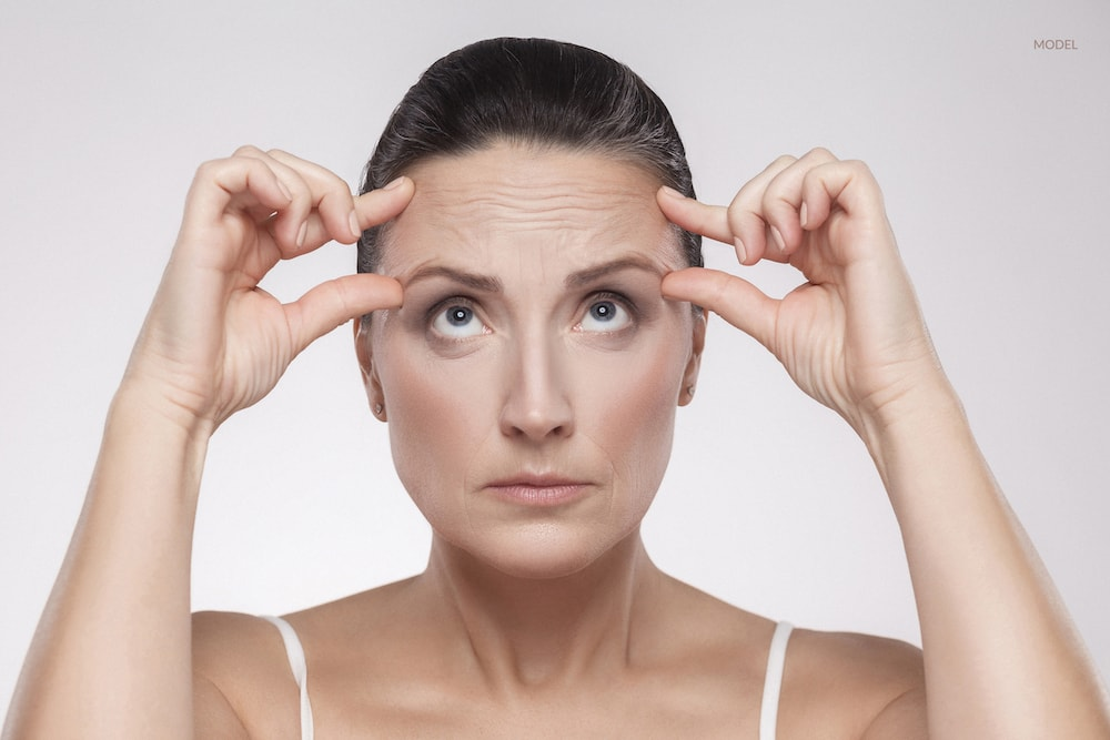 Women scrunching up her forehead, wondering if she could benefit from a cosmetic anti-aging treatment.