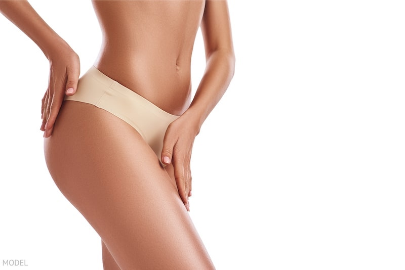 Close up image of thin woman's hips with her hands gently resting on skin.