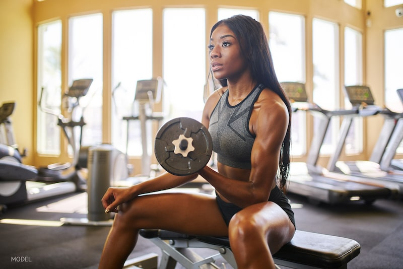 Very fit young woman lifting dumbbell weights in gym.