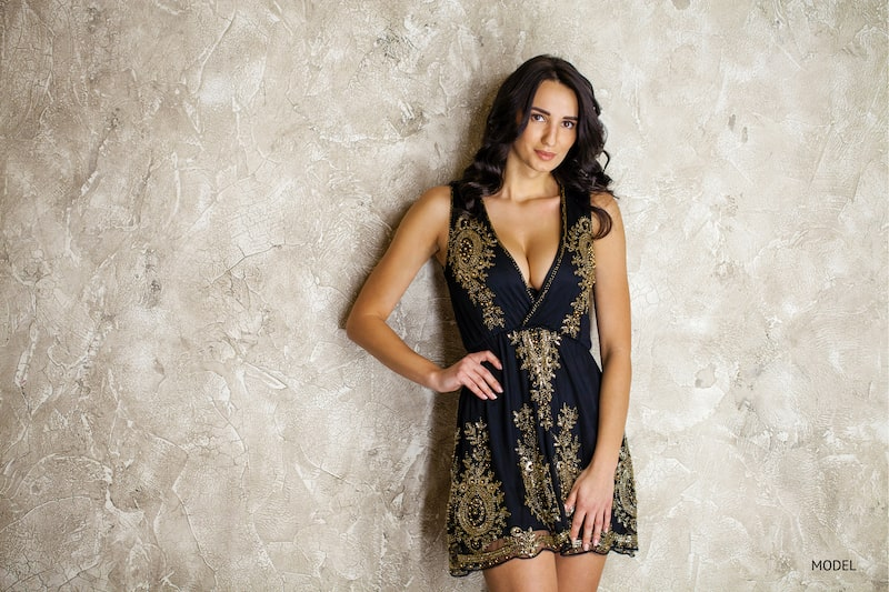 Woman wearing a plunging black dress with gold embellishments against a textured background.